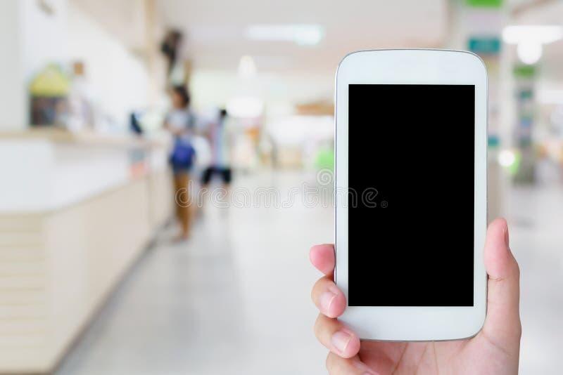 Κινητό τηλέφωνο λαβής χεριών με το θολωμένο νοσοκομείο στοκ εικόνες
