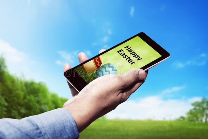 Κινητό τηλέφωνο εκμετάλλευσης ατόμων με ευτυχή εφαρμογή Πάσχας στοκ εικόνα
