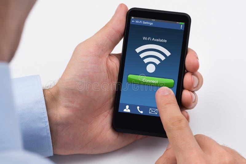 Κινητό τηλέφωνο εκμετάλλευσης χεριών προσώπου με το σήμα WiFi στοκ εικόνα