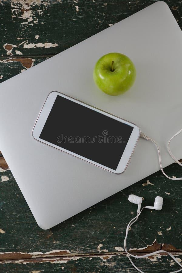 Κινητό τηλέφωνο και πράσινο μήλο στο lap-top στοκ εικόνες με δικαίωμα ελεύθερης χρήσης