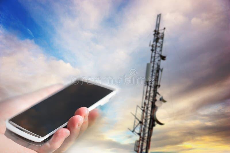 Κινητό τηλέφωνο που στοχεύει στον πύργο τηλεπικοινωνιών στοκ φωτογραφία