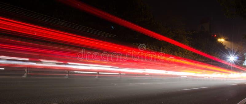 Κινούμενα αυτοκίνητα με το γρήγορα θολωμένο ίχνος των προβολέων στοκ φωτογραφία