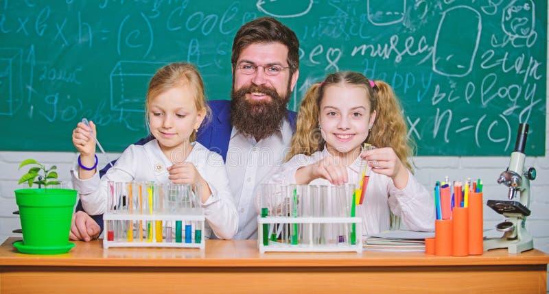 Κινούμενη επιστήμη προς τα εμπρός Επιστήμονες μικρών κοριτσιών που κρατούν τους σωλήνες δοκιμής στο μάθημα της φυσικής επιστήμης  στοκ εικόνες
