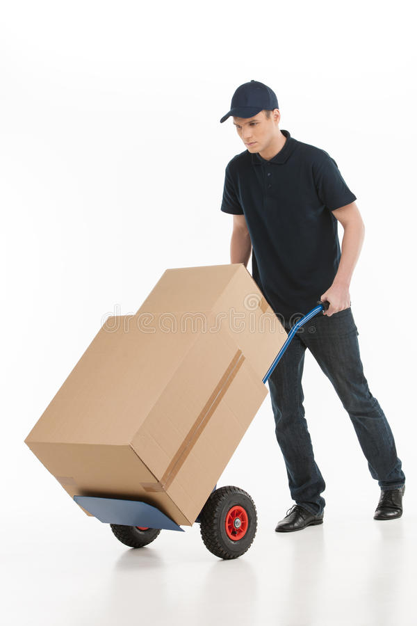 Κινούμενο σπίτι. Πλήρες μήκος νέου deliveryman με ένα φορτηγό χεριών στοκ εικόνες με δικαίωμα ελεύθερης χρήσης