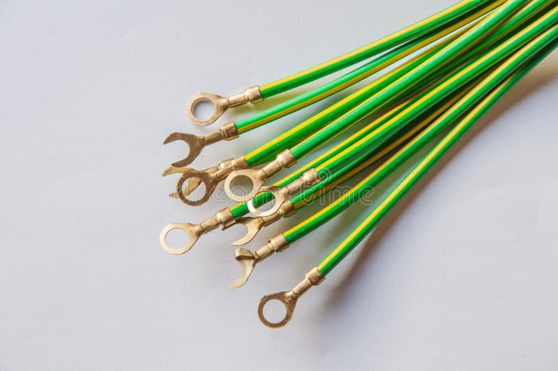 Κιτρινοπράσινο ηλεκτρικό καλώδιο με lug καλωδίων που απομονώνεται στο λευκό στοκ εικόνες