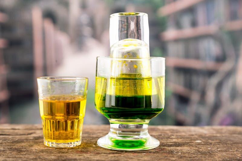 Κιτρινοπράσινο κοκτέιλ μέσα σε ένα γυαλί και έναν πυροβολισμό στοκ εικόνες