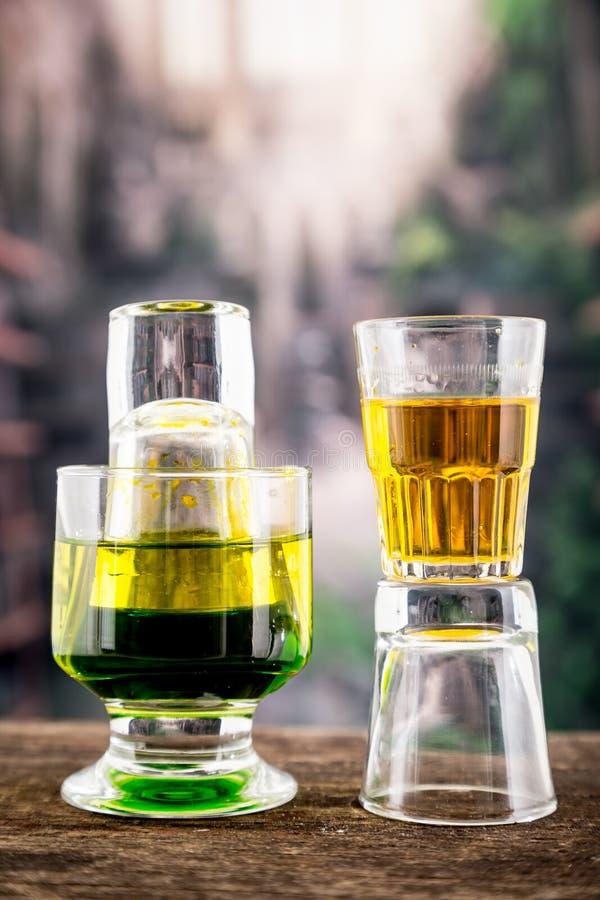 Κιτρινοπράσινο κοκτέιλ μέσα σε ένα γυαλί και έναν πυροβολισμό στοκ φωτογραφία με δικαίωμα ελεύθερης χρήσης
