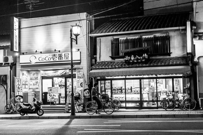 Κιότο, Ιαπωνία - 26 Δεκεμβρίου 2009: Ένα άτομο σε ένα ποδήλατο κοντά στο κατάστημα στην οδό Gion τη νύχτα στοκ εικόνες