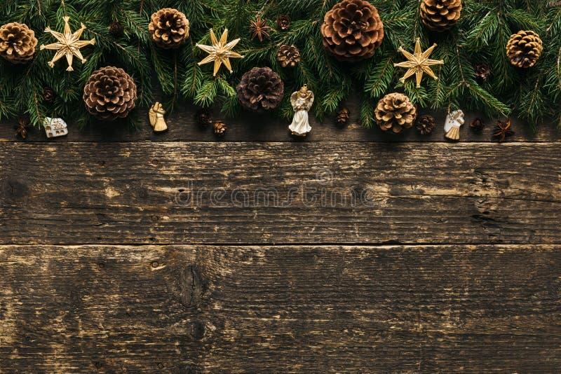 Κλάδοι δέντρων του FIR με τους κώνους πεύκων, τα μπιχλιμπίδια Χριστουγέννων και τις διακοσμήσεις στο ξύλινο υπόβαθρο, εορταστική  στοκ εικόνα
