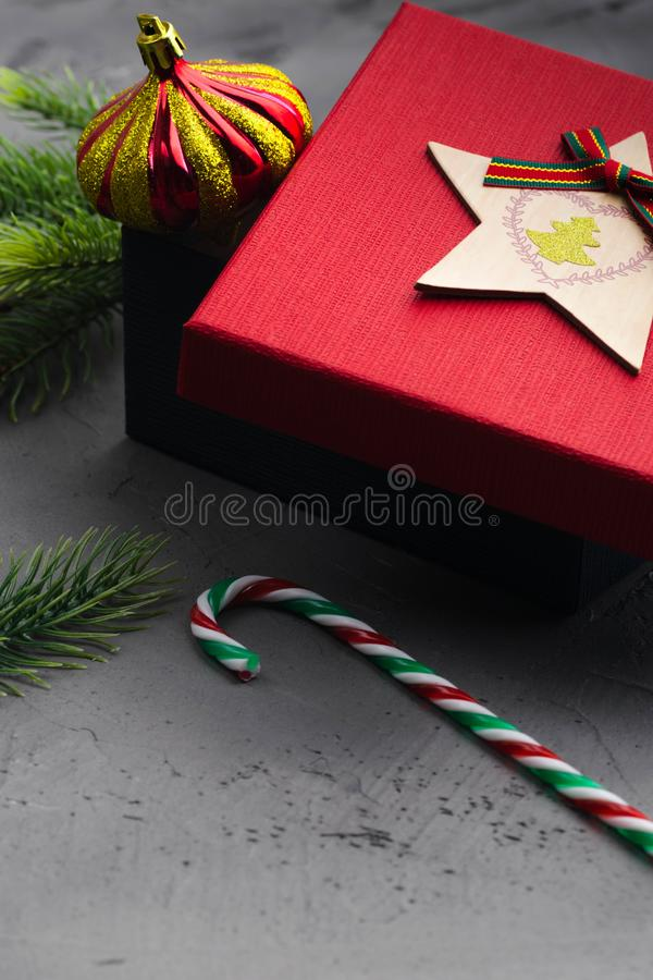 Κλάδοι του FIR στο συγκεκριμένο γκρίζο υπόβαθρο με το κόκκινες κιβώτιο και τις διακοσμήσεις δώρων νέο έτος Χριστουγέννων Επίπεδος στοκ φωτογραφίες με δικαίωμα ελεύθερης χρήσης