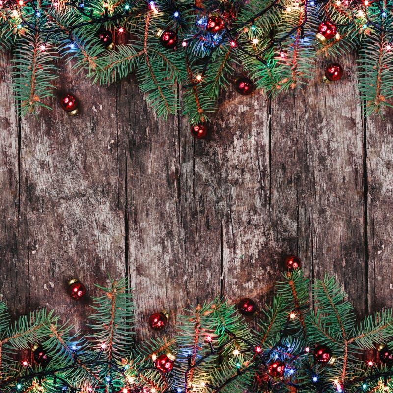 Κλάδοι του FIR Χριστουγέννων με τα φω'τα και κόκκινες διακοσμήσεις στο ξύλινο υπόβαθρο Χριστούγεννα και πλαίσιο καλής χρονιάς στοκ εικόνα με δικαίωμα ελεύθερης χρήσης