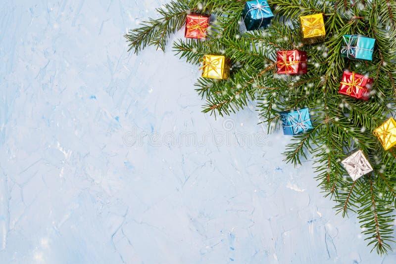 Κλάδος δέντρων έλατου Χριστουγέννων με τα μικρά δώρα στο μπλε υπόβαθρο διάστημα αντιγράφων στοκ φωτογραφία με δικαίωμα ελεύθερης χρήσης