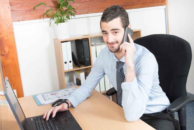 κλήση της συνεδρίασης τηλεφωνικών επιχειρηματιών στο γραφείο και χρησιμοποίηση του lap-top του εργαζόμενος στο νέο πρόγραμμα στοκ φωτογραφία με δικαίωμα ελεύθερης χρήσης