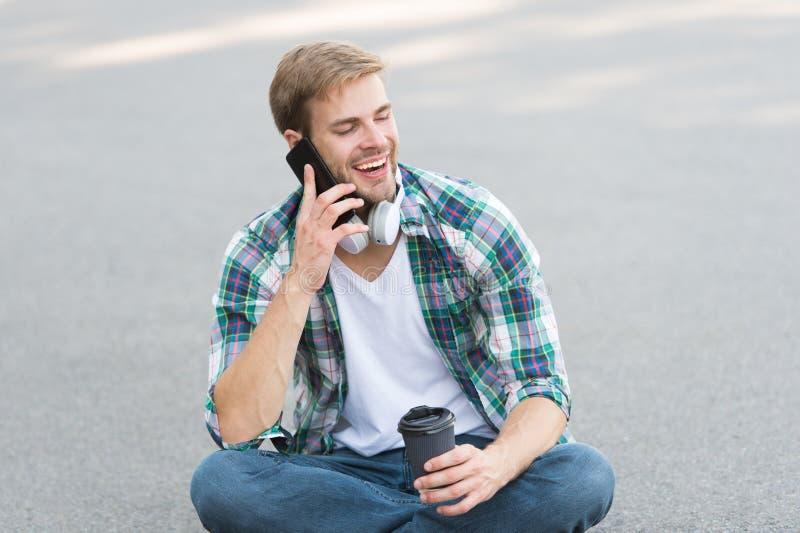 Κλήση φίλου Ο τύπος με τις φροντίδες του μαθητή απολαμβάνει τον καφέ του σε εξωτερικό χώρο Ισορροπία ζωής Υγεία Διάλειμμα για καφ στοκ εικόνες