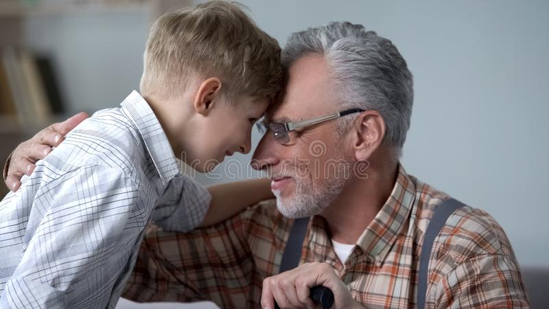 Κλίνοντας μέτωπα Granddad και αγοριών μαζί, επίσκεψη στο Σαββατοκύριακο, οικογενειακή αγάπη στοκ φωτογραφία με δικαίωμα ελεύθερης χρήσης