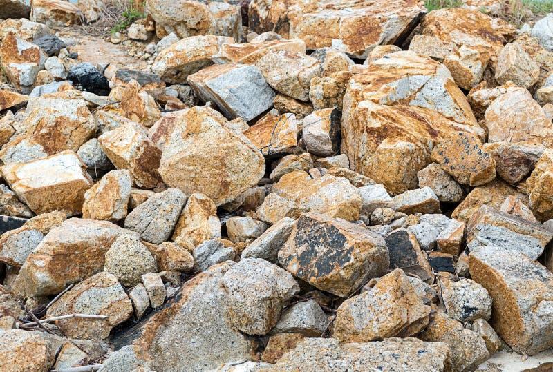Κλίση των μεγάλων ανώμαλων μπεζ γκρίζων πετρών πολύ μέρος κυβόλινθων του άγριου εγκαταλειμμένου promgulka υποβάθρου θέσεων στο βο στοκ φωτογραφία