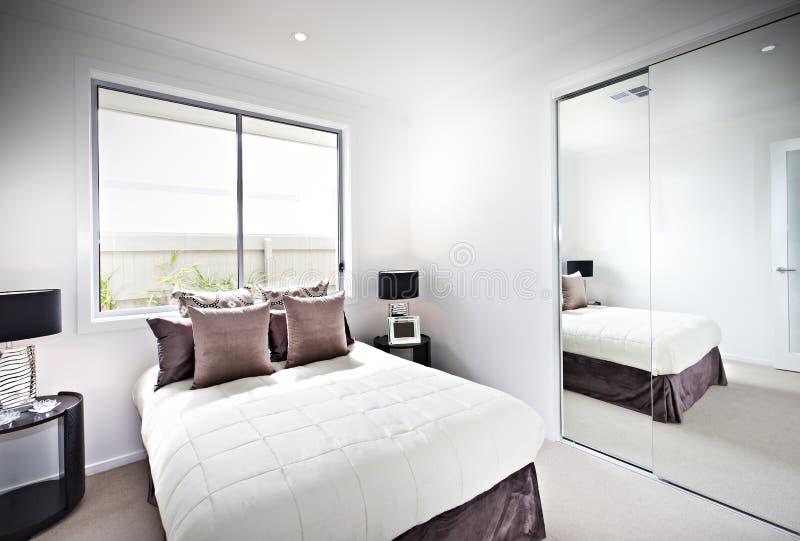 Κλασική κρεβατοκάμαρα με τα παράθυρα και τους λαμπτήρες εκτός από έναν καθρέφτη στοκ φωτογραφία