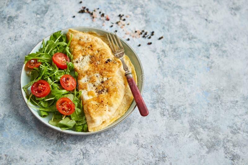 Κλασική ομελέτα αυγών που εξυπηρετείται με την ντομάτα κερασιών και τη σαλάτα arugula στην πλευρά στοκ εικόνες