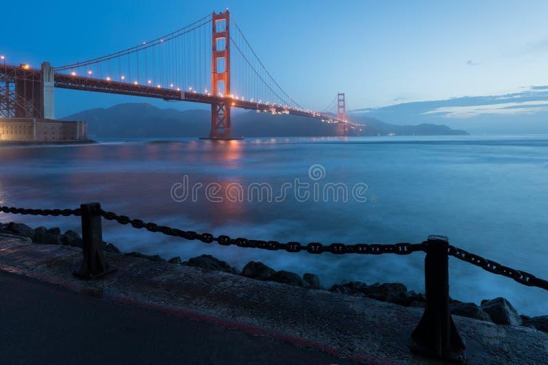 Κλασική πανοραμική άποψη της διάσημης χρυσής γέφυρας πυλών που βλέπει από το λιμάνι του Σαν Φρανσίσκο στο όμορφο φως βραδιού σε έ στοκ εικόνα