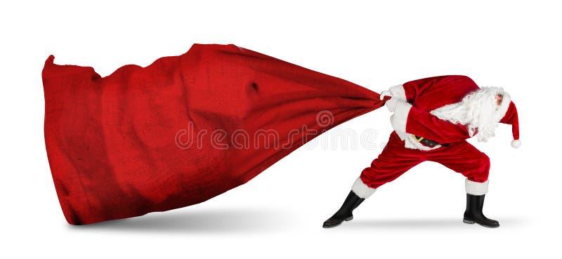 Κλασικός παραδοσιακός τρελός, αστείος άγιος βασίλης στην εξαντλητική υπηρεσία παράδοσης ρυμούλκηση τεράστιας μεγάλης κόκκινης σακ στοκ εικόνες