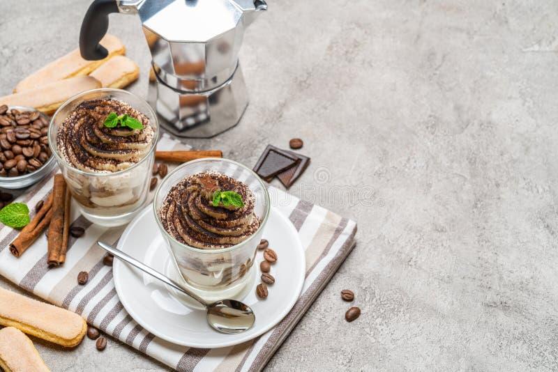 Κλασικό επιδόρπιο tiramisu σε ένα συγκεκριμένο υπόβαθρο γυαλιού και καφέ makeron στοκ εικόνα