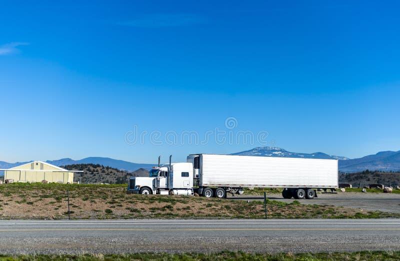 Κλασικό μεγάλο ημι φορτηγό εγκαταστάσεων γεώτρησης που μεταφέρει το φορτίο στην κατεψυγμένη ημι οδήγηση ρυμουλκών στο δρόμο στη Γ στοκ φωτογραφία με δικαίωμα ελεύθερης χρήσης