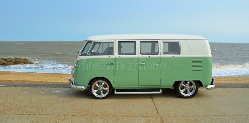 Κλασικό πράσινο και άσπρο φορτηγό τροχόσπιτων της VW που σταθμεύουν στον περίπατο προκυμαιών παραλία και θάλασσα στο υπόβαθρο στοκ φωτογραφία με δικαίωμα ελεύθερης χρήσης