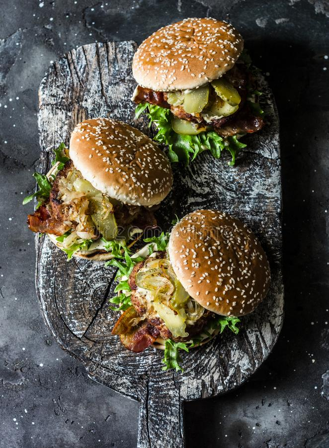 Κλασικό σπιτικό burger με cutlet χοιρινού κρέατος, μπέϊκον, τουρσιά, τηγάνισε τα κρεμμύδια και τη σάλτσα μουστάρδας μαγιονέζας στ στοκ φωτογραφία με δικαίωμα ελεύθερης χρήσης