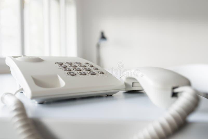 Κλασσικό άσπρο τηλέφωνο γραμμών εδάφους με το δέκτη από το γάντζο στοκ εικόνες