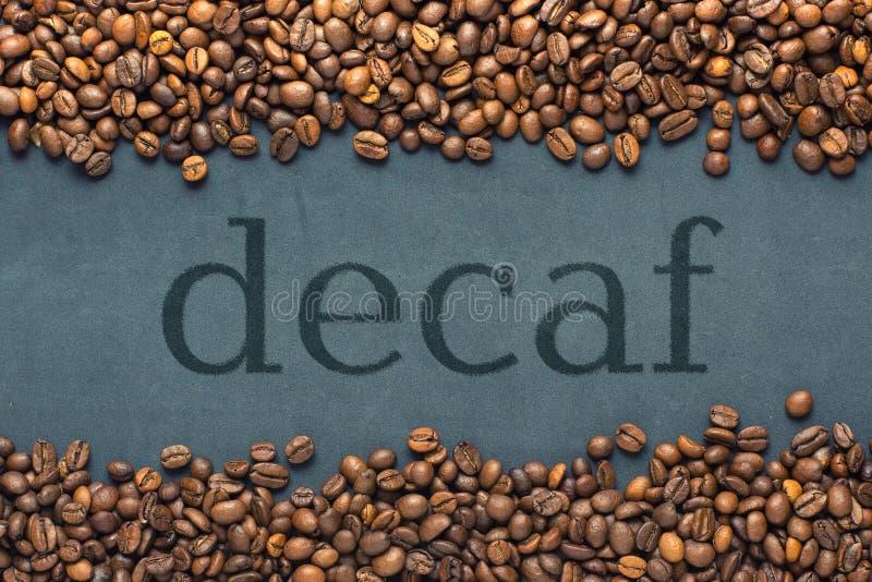 Κλείσιμο κόκκων καφέ στο γκρι φόντο με την επιγραφή decaf στοκ φωτογραφία με δικαίωμα ελεύθερης χρήσης