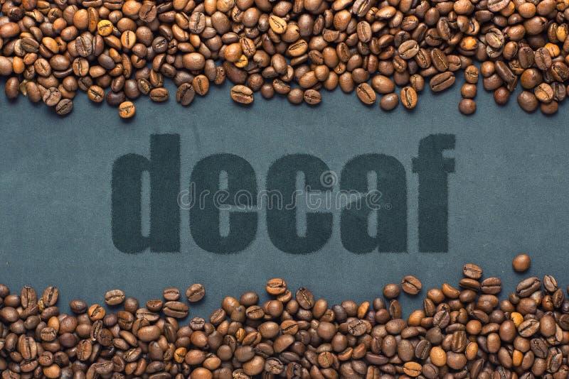 Κλείσιμο κόκκων καφέ στο γκρι φόντο με την επιγραφή decaf στοκ εικόνα