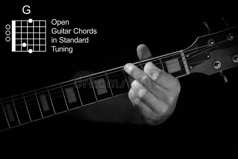Κλείσιμο του χεριού που παίζει χορδή G στην κιθάρα στοκ εικόνα