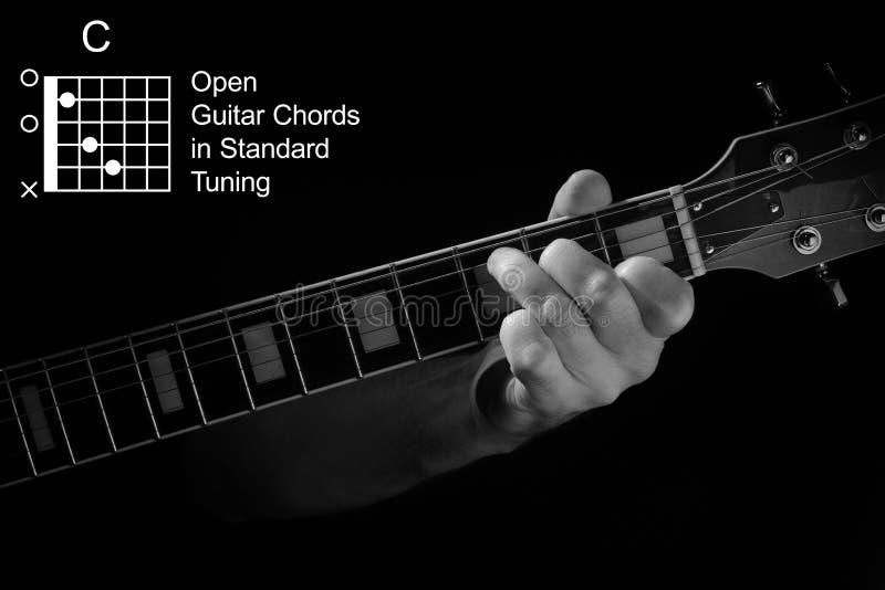 Κλείσιμο του χεριού που παίζει C χορδή στην κιθάρα στοκ φωτογραφίες