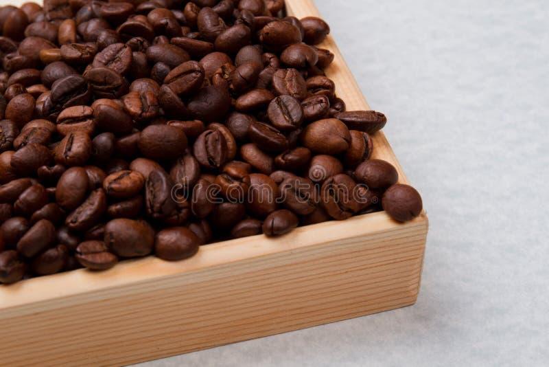 Κλείστε ένα σωρό φρυγμένους κόκκους καφέ σε ξύλινη μορφή στοκ εικόνες