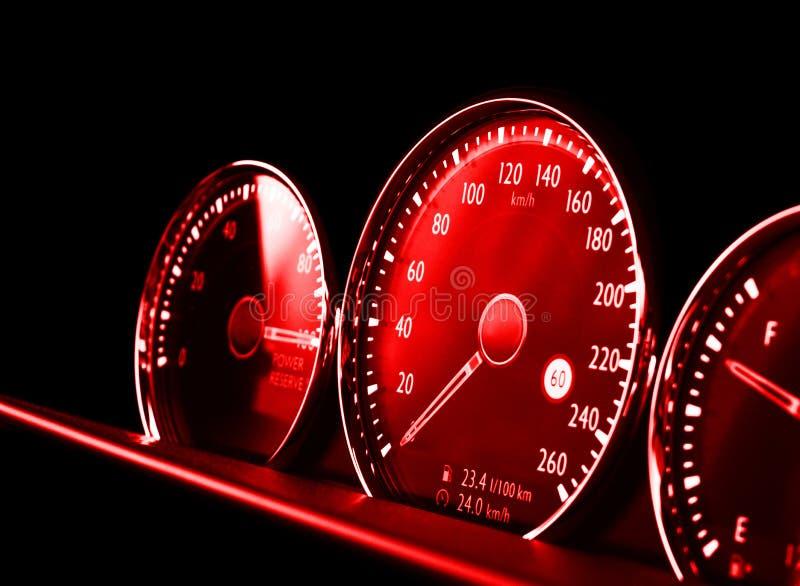 Κλείστε αυξημένος ενός κόκκινου ταχυμέτρου σε ένα αυτοκίνητο Ταμπλό αυτοκινήτων Λεπτομέρειες ταμπλό με τους λαμπτήρες ένδειξης Επ στοκ εικόνα