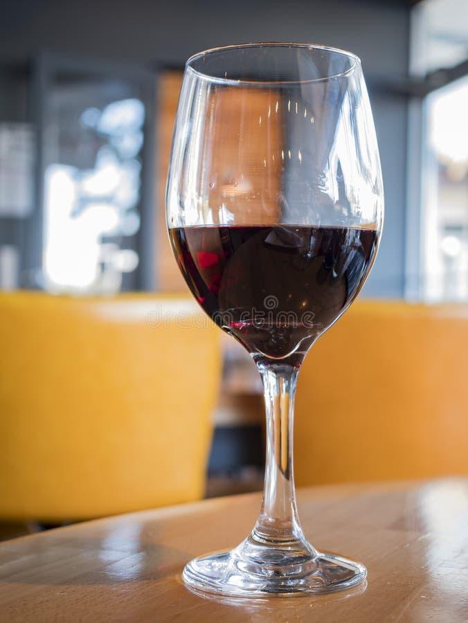 Κλείστε αυξημένος ενός ποτηριού του κόκκινου κρασιού στοκ εικόνα