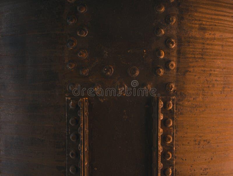 Κλείστε αυξημένος μιας μεγάλης σκουριασμένης δεξαμενής με το μπουλόνι που καθορίζεται με τα κομμάτια μετάλλων στοκ εικόνες