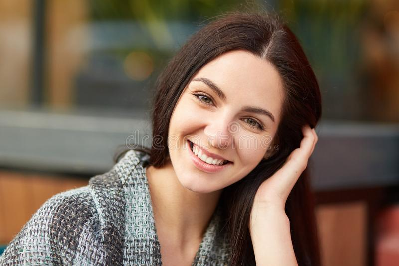 Κλείστε αυξημένος της ευχάριστης κοιτάζοντας γυναίκας brunette με το γοητευτικό ελκυστικό χαμόγελο, που τυλίγεται στο coverlet, π στοκ εικόνα με δικαίωμα ελεύθερης χρήσης