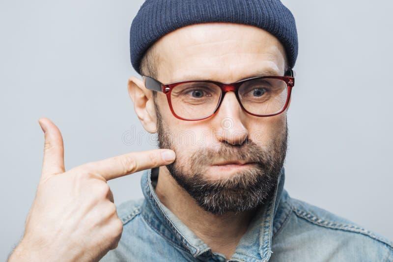 Κλείστε αυξημένος του αξύριστου αρσενικού με τα παχιά μάγουλα γενειάδων και mustache χτυπημάτων και δείχνει με το πρόσθιο δάχτυλο στοκ εικόνες με δικαίωμα ελεύθερης χρήσης