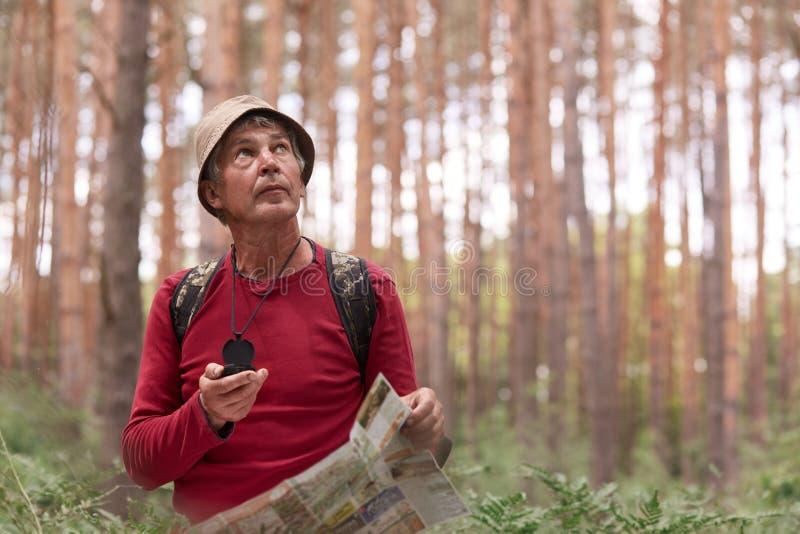 Κλείστε αυξημένος του ατόμου eldery που και που εξετάζει επάνω τον ουρανό, χρησιμοποιώντας το χάρτη και την πυξίδα για την κατεύθ στοκ εικόνες με δικαίωμα ελεύθερης χρήσης