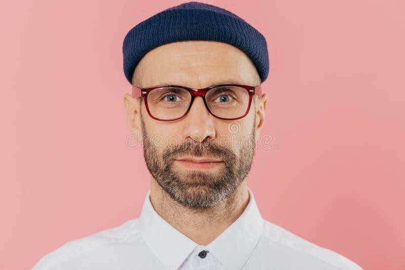 Κλείστε αυξημένος του βέβαιου άνδρα υπάλληλος με την παχιά γενειάδα και mustache, φορά τα διαφανή γυαλιά, καπέλο, άσπρο πουκάμισο στοκ φωτογραφίες με δικαίωμα ελεύθερης χρήσης
