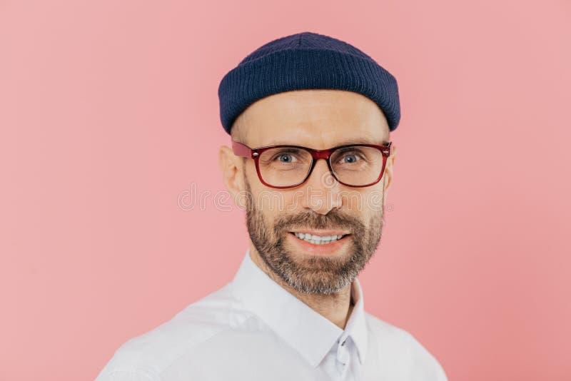 Κλείστε αυξημένος του ευχάριστου κοιτάζοντας αξύριστου ατόμου φορά τα γυαλιά, έχει το ευγενές χαμόγελο, εξετάζει με τη ικανοποιημ στοκ εικόνα