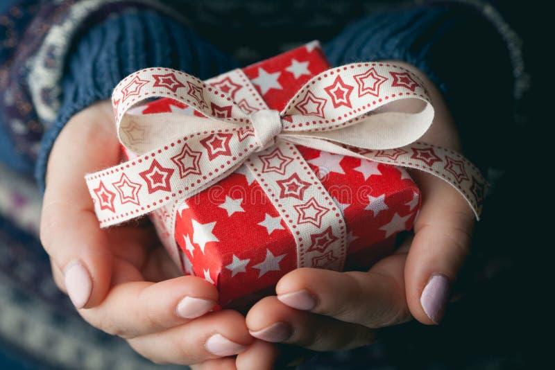 Κλείστε αυξημένος των θηλυκών χεριών κρατώντας ένα μικρό δώρο στοκ φωτογραφία με δικαίωμα ελεύθερης χρήσης