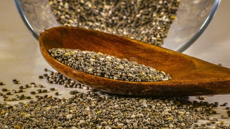 Κλείστε αυξημένος των σπόρων chia στο γυαλί και το κουτάλι στοκ φωτογραφίες