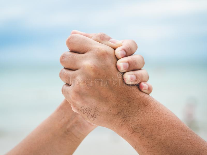 Κλείστε δύο κρατώντας τα χέρια στο υπόβαθρο θάλασσας bokeh Φιλία, Hel στοκ εικόνα με δικαίωμα ελεύθερης χρήσης