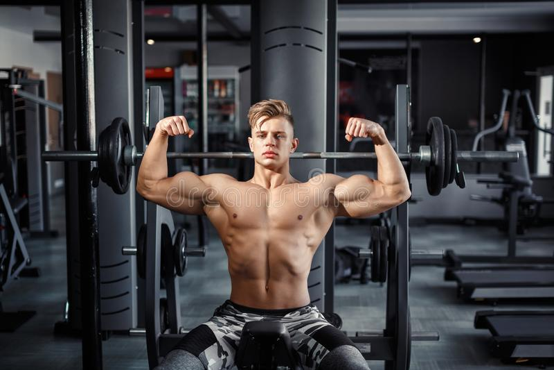 Κλείστε επάνω βαρών μιας των μυϊκών νεαρών άνδρων ανύψωσης στη γυμναστική στο σκοτεινό υπόβαθρο στοκ φωτογραφία με δικαίωμα ελεύθερης χρήσης
