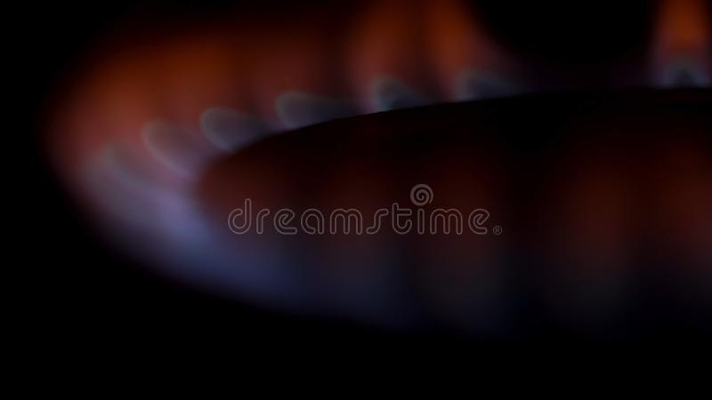 Κλείστε επάνω για τα εγκαύματα φυσικού αερίου στη σόμπα κουζινών στο σκοτάδι μέσα Κόκκινη και μπλε φλόγα του καυστήρα αερίου, μαγ στοκ εικόνες