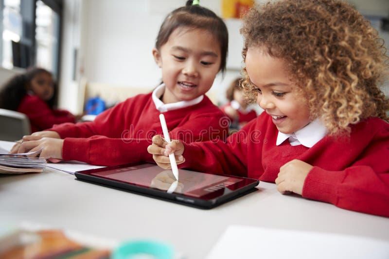 Κλείστε επάνω δύο μαθητριών παιδικών σταθμών που φορούν τις σχολικές στολές, καθμένος σε ένα γραφείο σε μια τάξη χρησιμοποιώντας  στοκ εικόνα με δικαίωμα ελεύθερης χρήσης