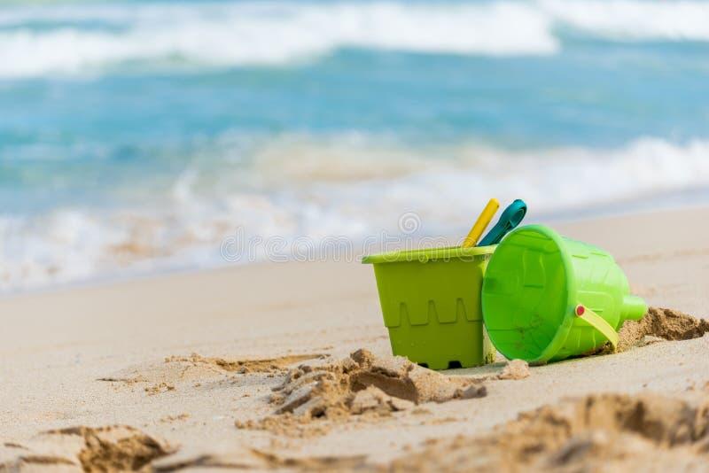 Κλείστε επάνω δύο πράσινων παιχνιδιών άμμου children's με τους κάδους και των φτυαριών σε μια αμμώδη παραλία στη Χαβάη στοκ εικόνα με δικαίωμα ελεύθερης χρήσης