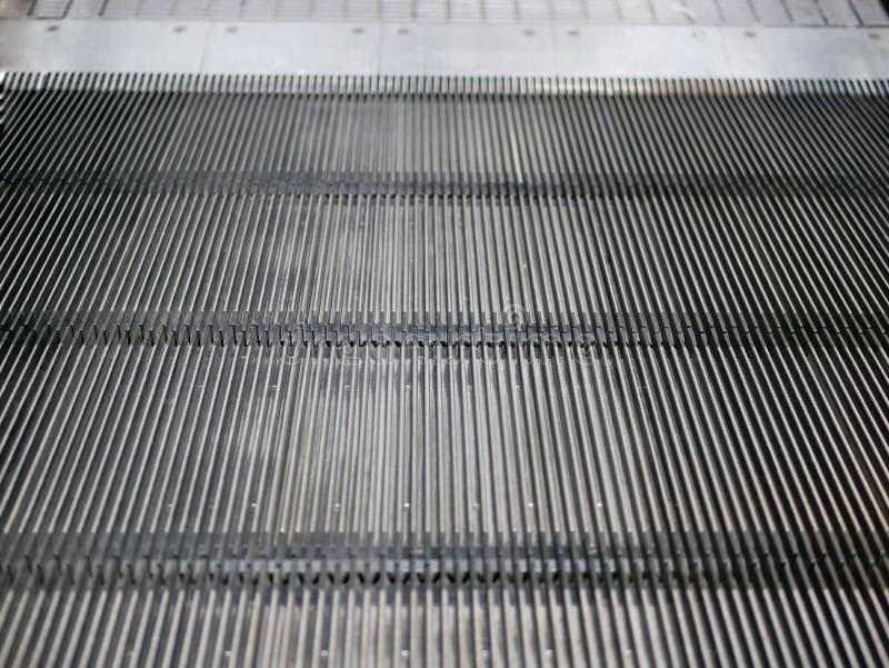 Κλείστε επάνω ενός κινούμενου καροτσακιού αγορών τα βήματα κυλιόμενων σκαλών ` s στοκ εικόνα με δικαίωμα ελεύθερης χρήσης